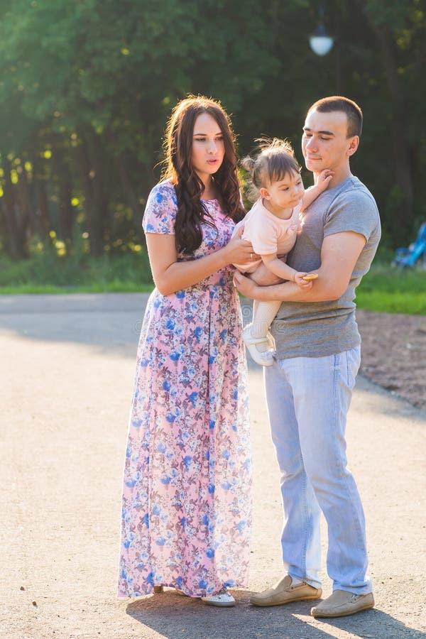 Glückliche Mischrennen-Familie, die für ein Portrait im Park aufwirft stockfotos