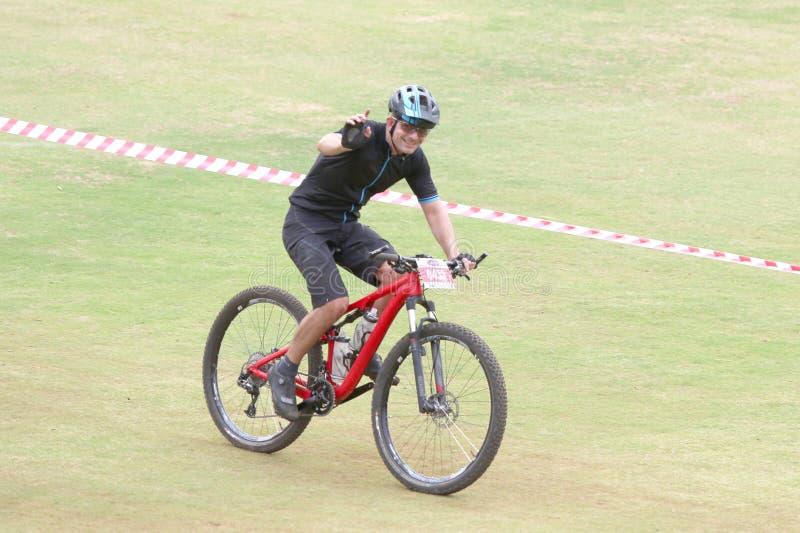Glückliche Mitte alterte den Mann, der zur Ziellinie an der Mountainbike reitet lizenzfreie stockfotos