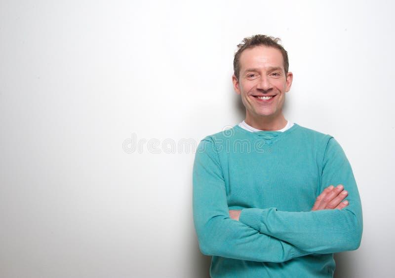 Glückliche Mitte gealterter Mann, der mit den Armen gekreuzt lächelt stockfoto