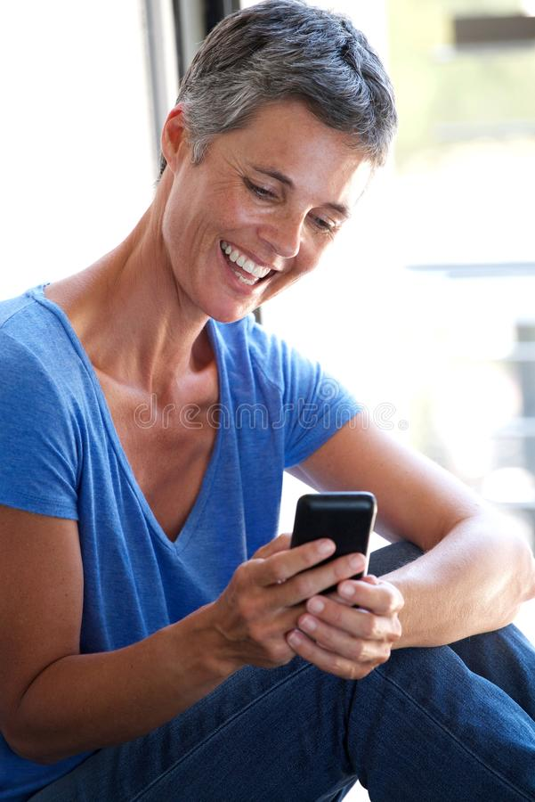 Glückliche Mittelalterfrau, die Mobiltelefon durch Fenster verwendet stockbilder