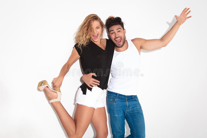 Glückliche Modepaare, die zusammen springen und schreien lizenzfreies stockbild