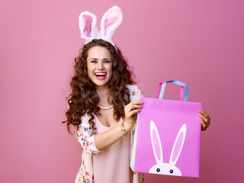 Glückliche moderne Frau auf rosa darstellender Ostern-Einkaufstasche lizenzfreie stockfotografie