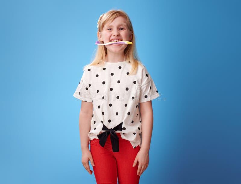 Glückliche moderne Mädchenholdingzahnbürste in ihren Zähnen auf Blau lizenzfreie stockfotos