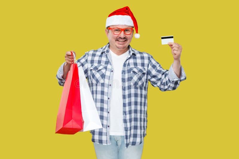 Glückliche moderne Mitte der zufälligen Art alterte Mann in roter Kappe des neuen Jahres, e stockfoto