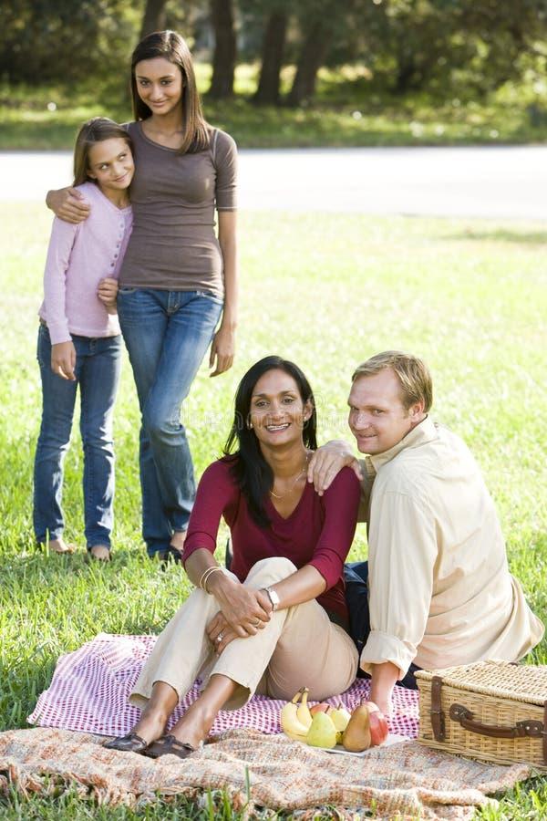 Glückliche moderne multikulturelle Familie, die Picknick genießt stockfotografie