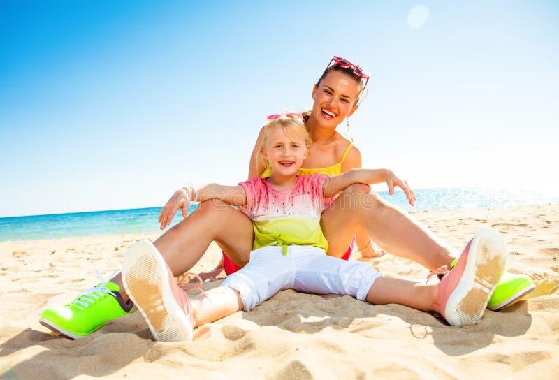Glückliche moderne Mutter und Tochter, die auf Seeküste sitzt lizenzfreie stockfotos