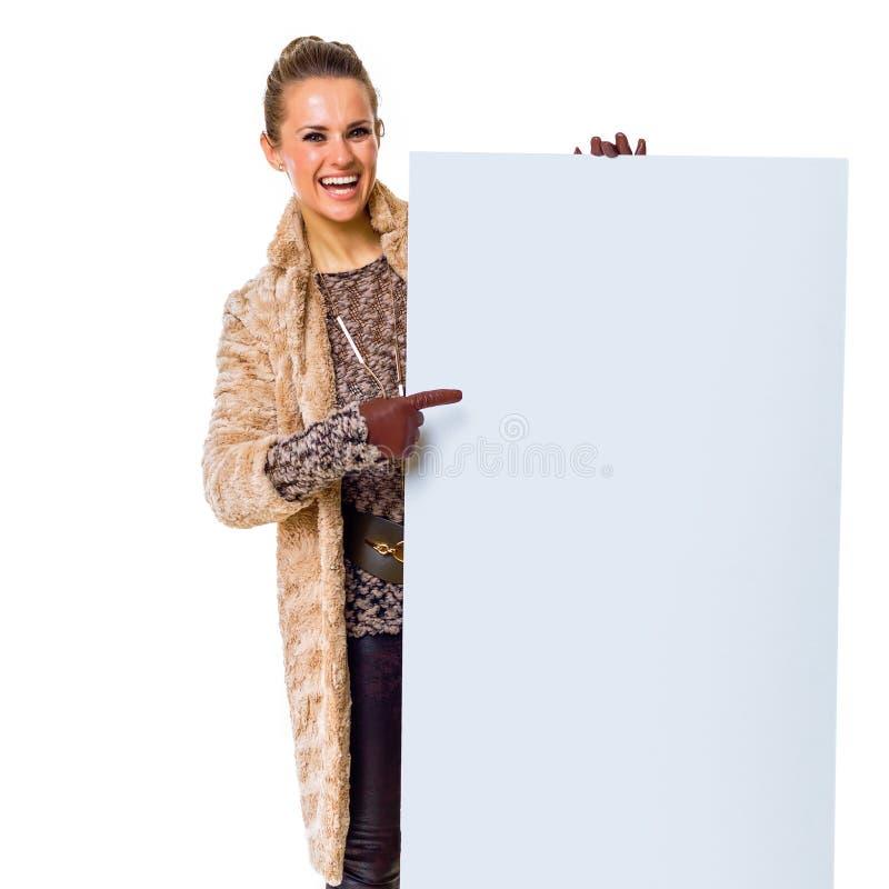Glückliche modische Frau auf dem weißem Zeigen auf leeres Brett stockfoto