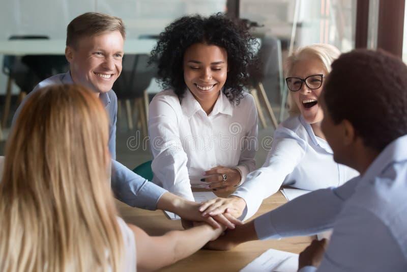 Glückliche multi ethnische Angestellte, welche die Hände teilgenommen an Teamentwicklung stapeln lizenzfreie stockfotos
