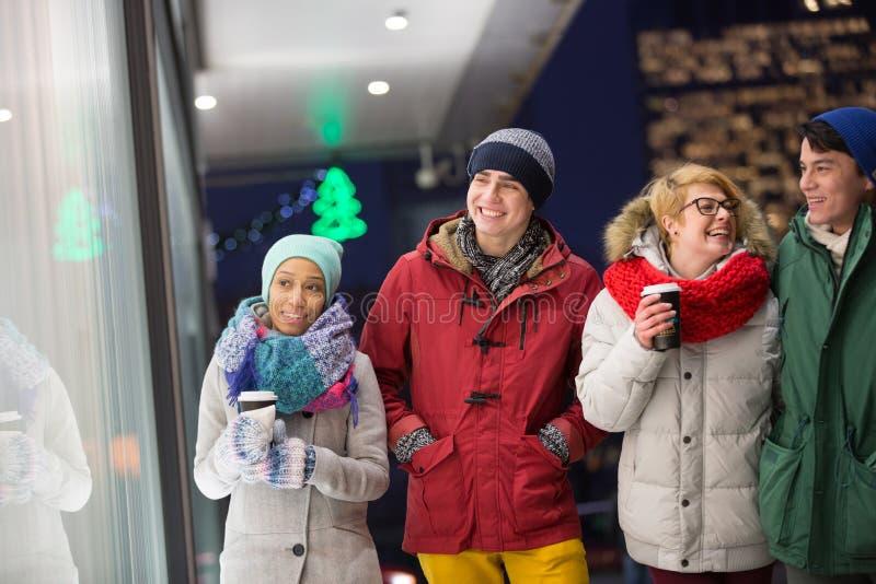 Glückliche multiethnische Freunde im Winter tragen das Gehen in Stadt während der Dämmerung lizenzfreie stockbilder