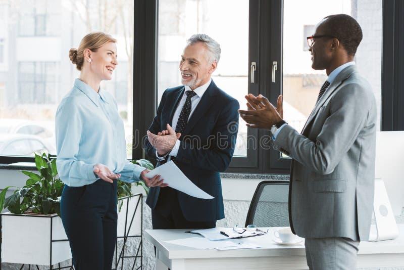 glückliche multiethnische Geschäftsmänner, die zur netten Geschäftsfrau applaudieren lizenzfreie stockbilder