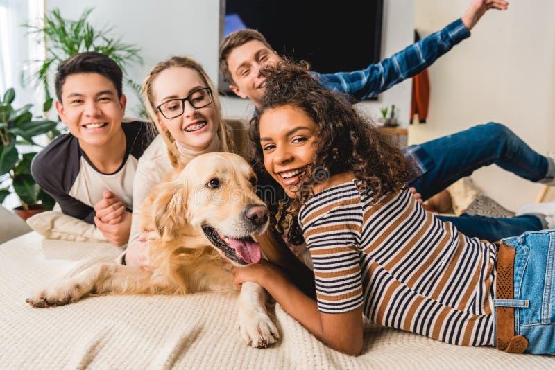 glückliche multiethnische Jugendliche, die Hund und das Schauen palming sind lizenzfreie stockbilder