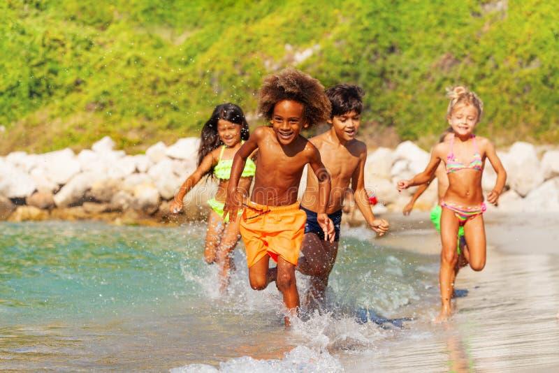 Glückliche multiethnische Kinder, die Spaß an der Küste haben lizenzfreie stockbilder
