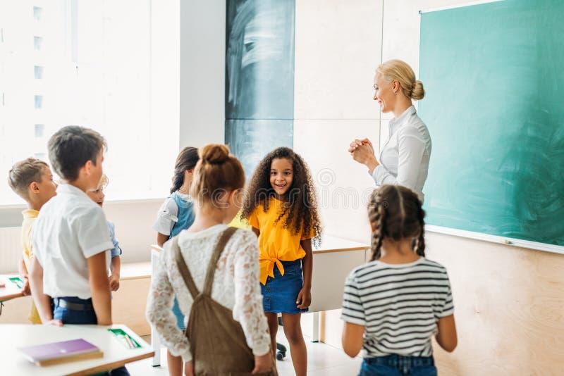 glückliche multiethnische Mitschüler, die um Lehrer stehen stockfotos