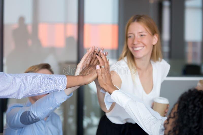 Glückliche multikulturelle Angestellte geben hoch fünf zusammen, Fokus auf Händen stockbild