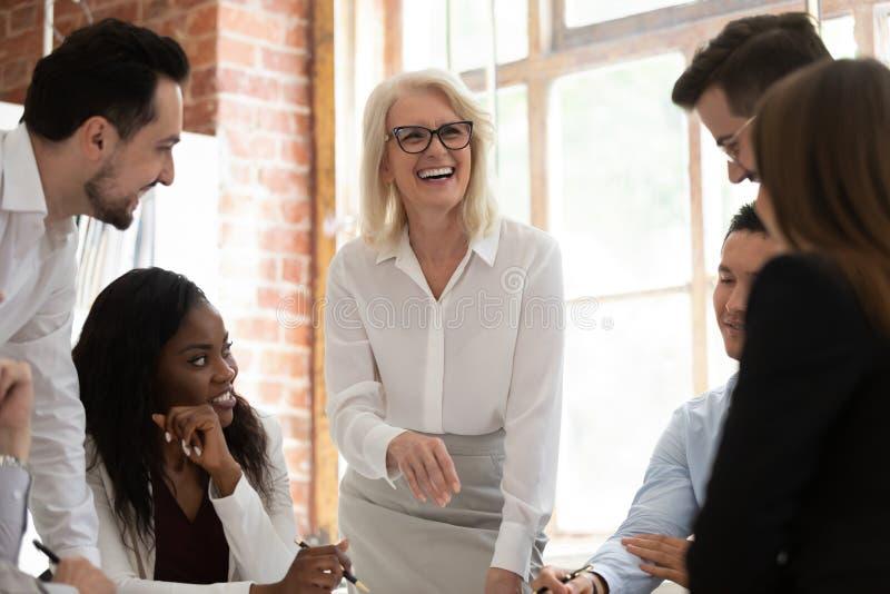 Glückliche multikulturelle junge Angestellte mit lachendem zusammenarbeiten des alten Mentors stockbild