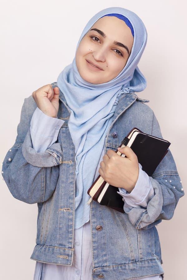 Glückliche muslimische Geschäftsfrau feiert ihren ersten Erfolg im Geschäftsleben Attraktive muslimische Studierende halten Noteb stockbild
