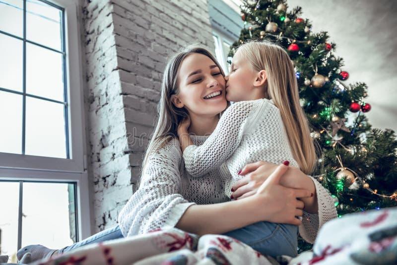 Glückliche Mutter beglückwünscht das Kind mit einem guten Rutsch ins Neue Jahr und einem Weihnachten lizenzfreies stockbild