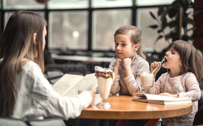 Glückliche Mutter der jungen Frauen mit den Kindern, die ein Milchshaken trinken stockbilder
