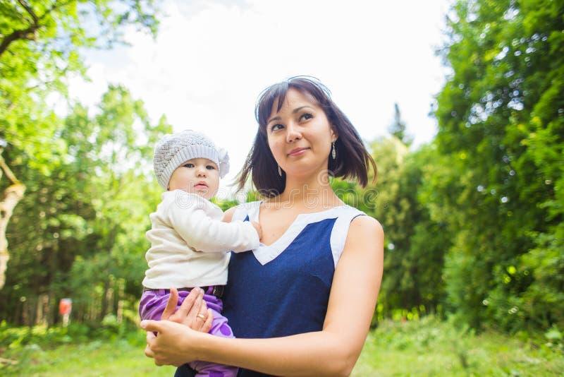Glückliche Mutter der Mischrasse mit Porträt des Babys draußen stockfotografie