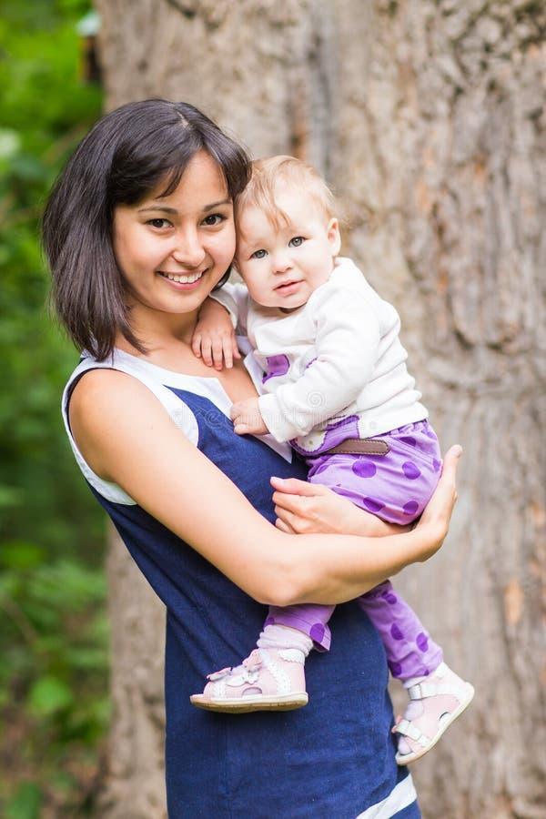 Glückliche Mutter der Mischrasse mit Porträt des Babys draußen stockfotos