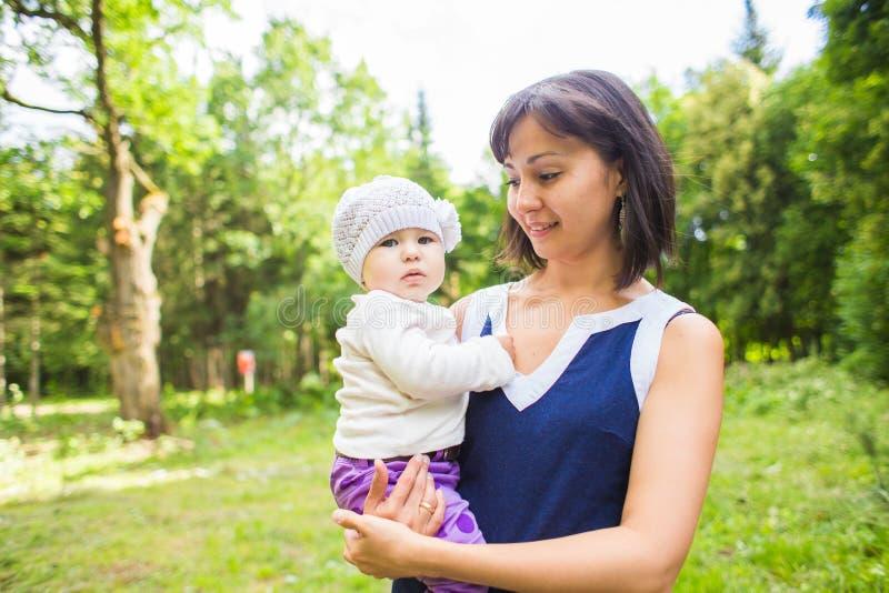 Glückliche Mutter der Mischrasse mit Porträt des Babys draußen stockbilder