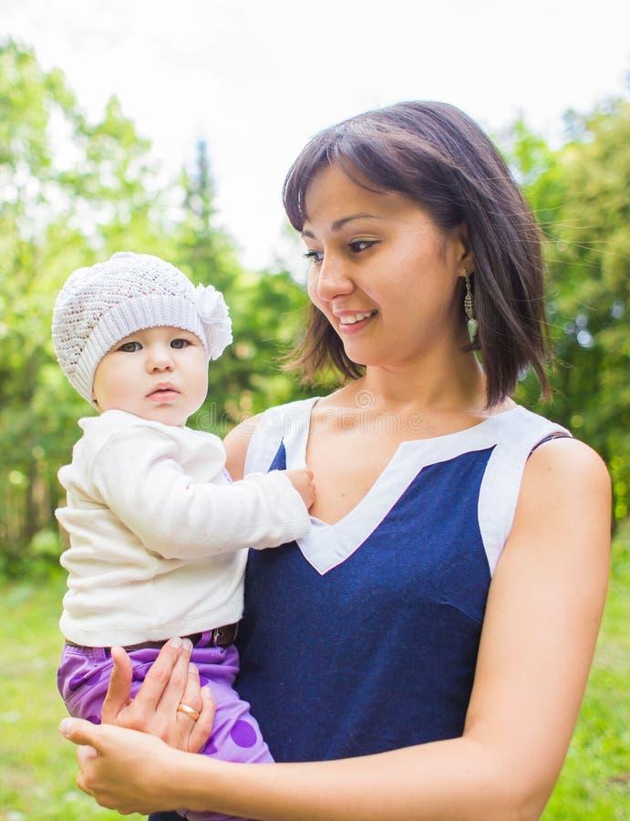 Glückliche Mutter der Mischrasse mit Porträt des Babys draußen stockbild
