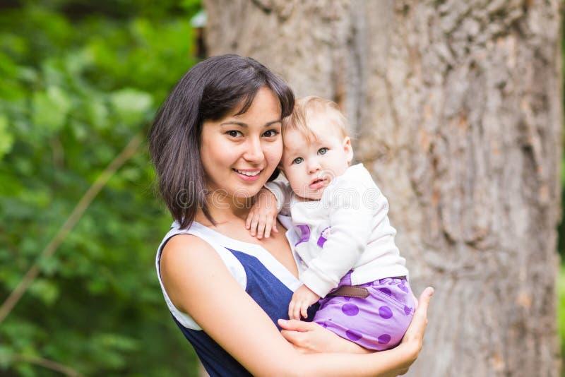 Glückliche Mutter der Mischrasse mit Porträt des Babys draußen lizenzfreies stockbild