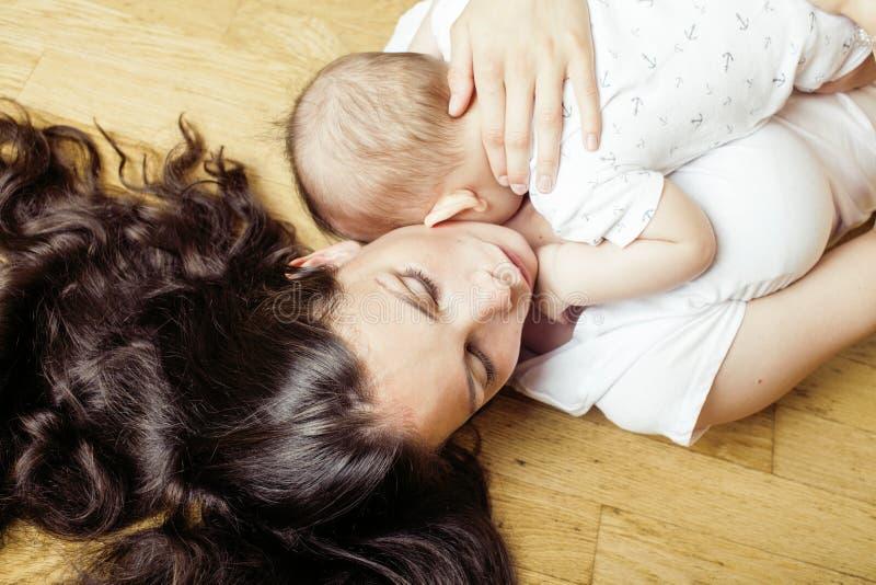 Glückliche Mutter des jungen Brunette, die Kleinkindbabysohn, stillend Konzept, moderne Leute des Lebensstils hält stockbilder