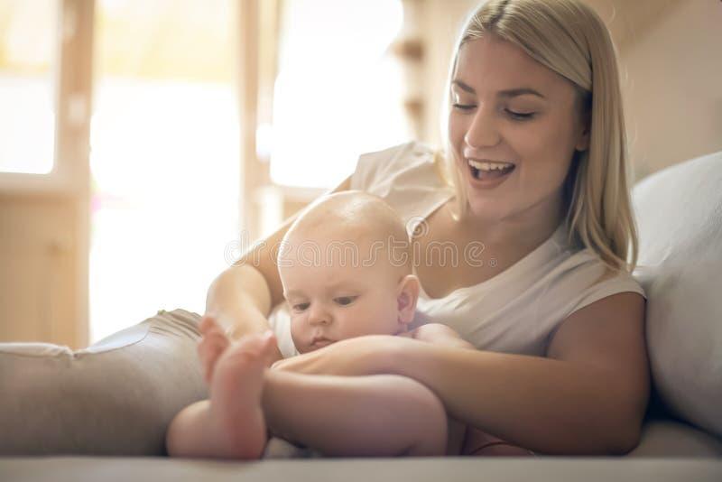 Glückliche Mutter des smiley mit Baby zu Hause lizenzfreie stockfotografie