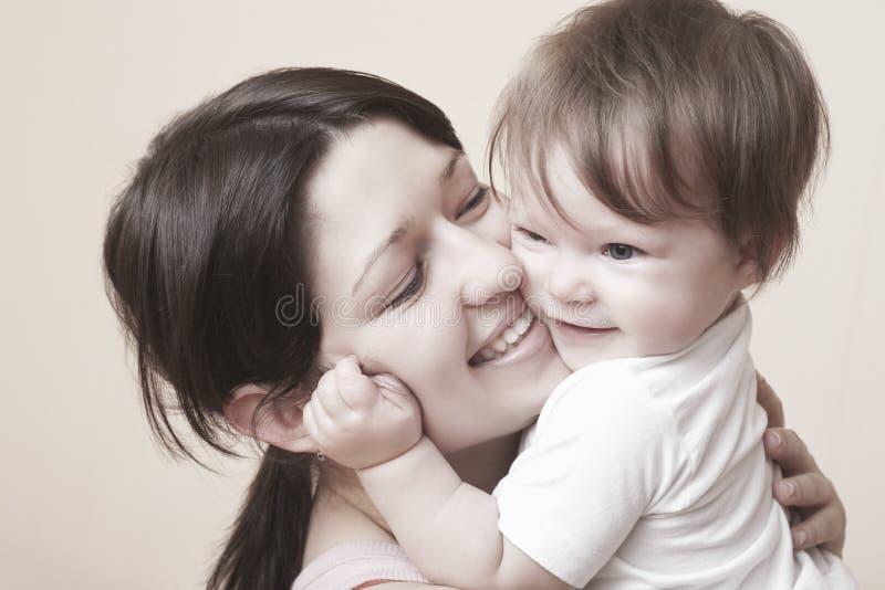 Glückliche Mutter, die Baby umarmt stockfoto
