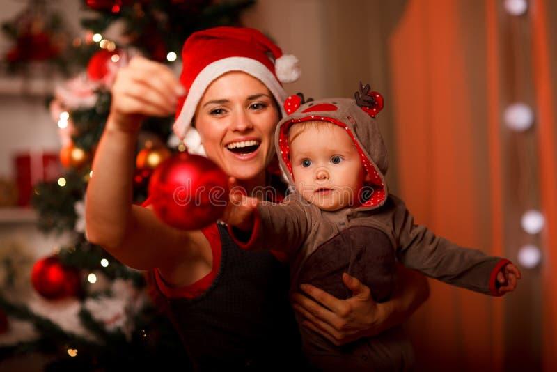 Glückliche Mutter, die dem Schätzchen Weihnachtskugel zeigt stockbilder