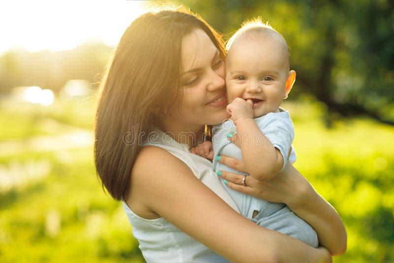 Glückliche Mutter, die ein junges Sohnsonnenlicht hält lizenzfreies stockfoto
