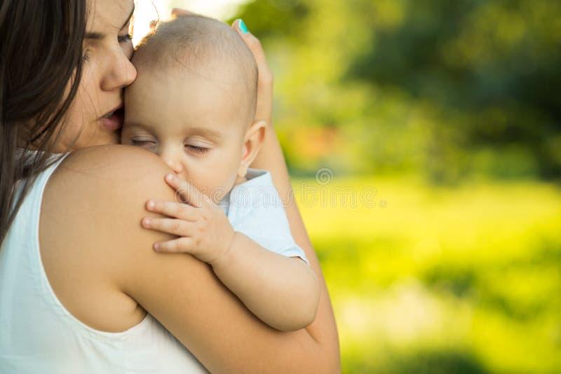 Glückliche Mutter, die einen jungen schlafenden Sohn hält lizenzfreies stockfoto