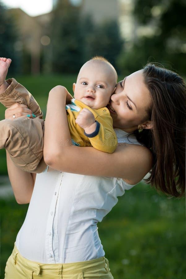 Glückliche Mutter, die einen jungen Sohn hält lizenzfreies stockfoto