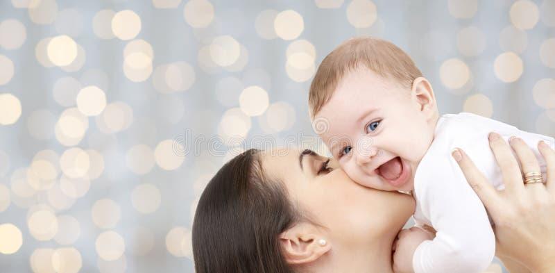 Glückliche Mutter, die ihr Baby über Lichtern küsst stockfotos