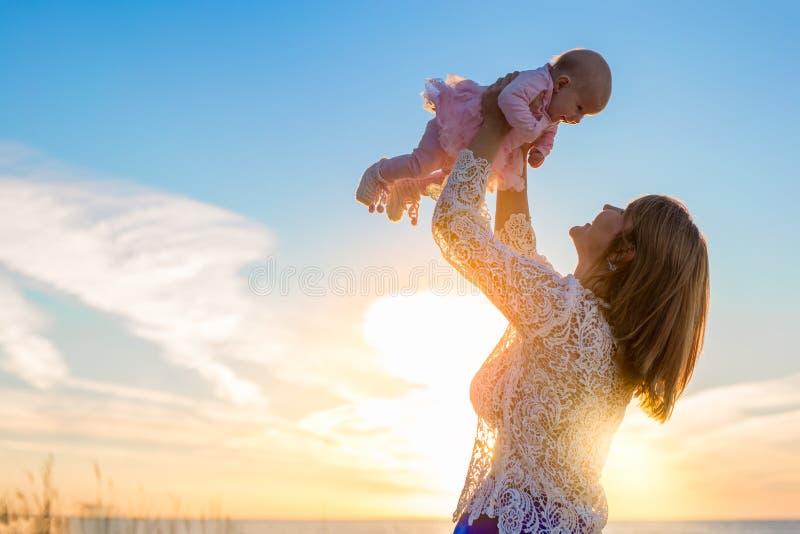 Glückliche Mutter, die ihr nettes Baby bei Sonnenuntergang hält stockbilder
