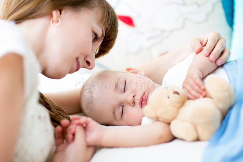 Glückliche Mutter, die ihr neugeborenes Baby streichelt lizenzfreies stockfoto