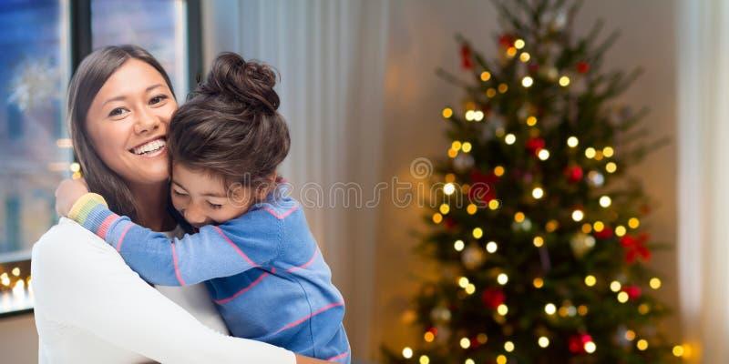 Glückliche Mutter, die ihre Tochter auf Weihnachten umarmt lizenzfreie stockbilder