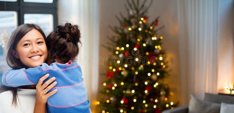 Glückliche Mutter, die ihre Tochter auf Weihnachten umarmt lizenzfreies stockbild