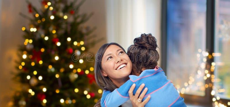 Glückliche Mutter, die ihre Tochter auf Weihnachten umarmt lizenzfreie stockfotografie
