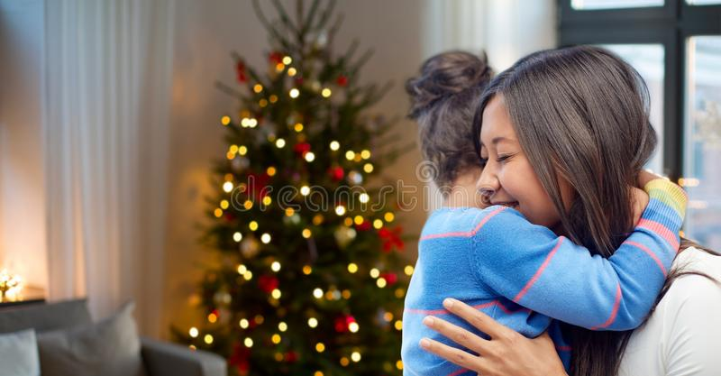 Glückliche Mutter, die ihre Tochter auf Weihnachten umarmt stockbild