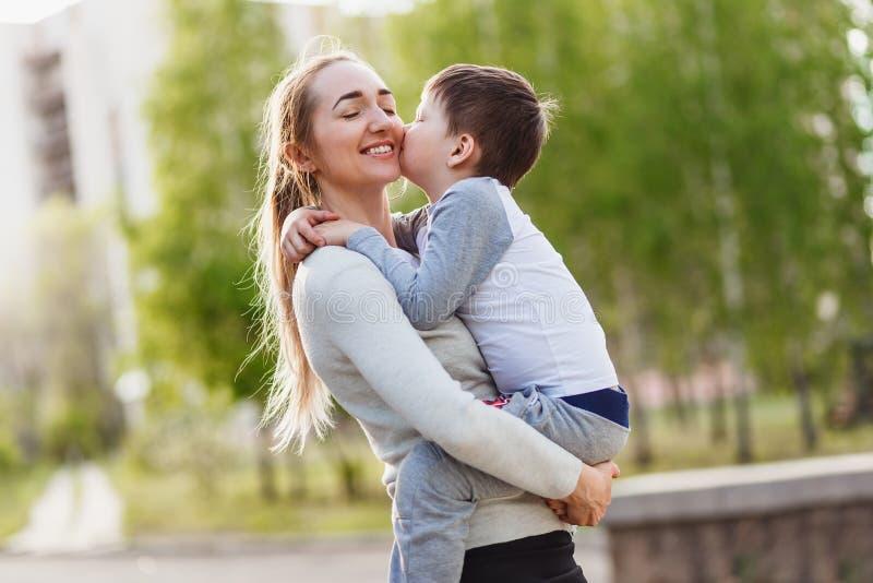 Glückliche Mutter, die ihren kleinen Sohn im Sommer im Freien umarmt lizenzfreies stockfoto