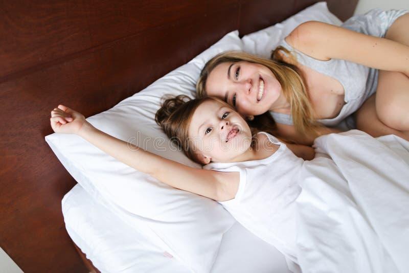 Glückliche Mutter, die im Bett mit kleiner fröhlicher Tochter liegt lizenzfreie stockfotografie