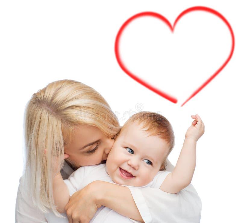 Glückliche Mutter, die lächelndes Baby küsst lizenzfreie stockbilder