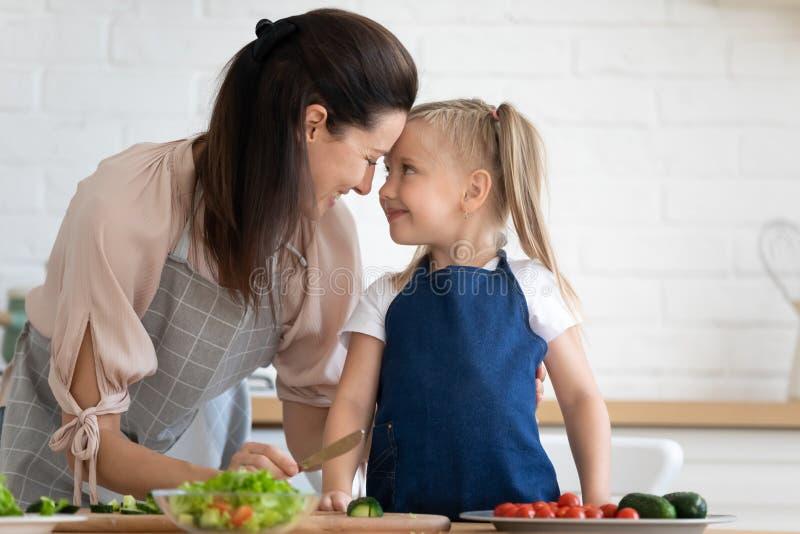 Glückliche Mutter, die Liebe und Hingabe an die Tochter in der Küche ausdrückt stockfotos