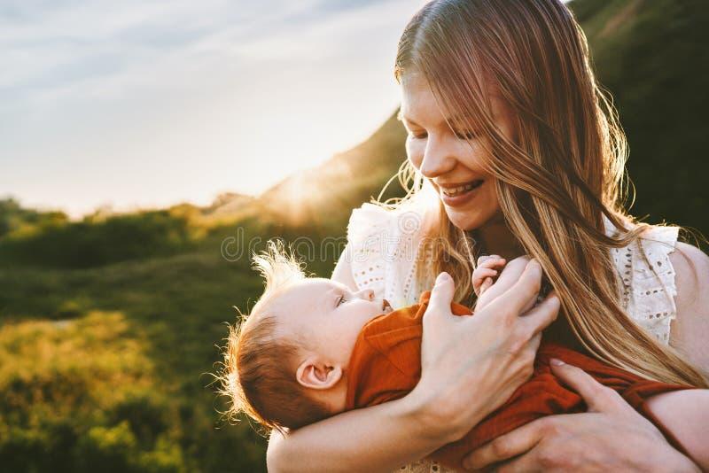 Gl?ckliche Mutter, die mit Familienlebensstil des S?uglingsbabys im Freien geht lizenzfreies stockbild