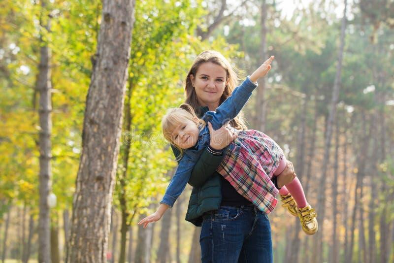 Glückliche Mutter, die mit seiner Tochter im Park am Sommertag spielt stockfotografie