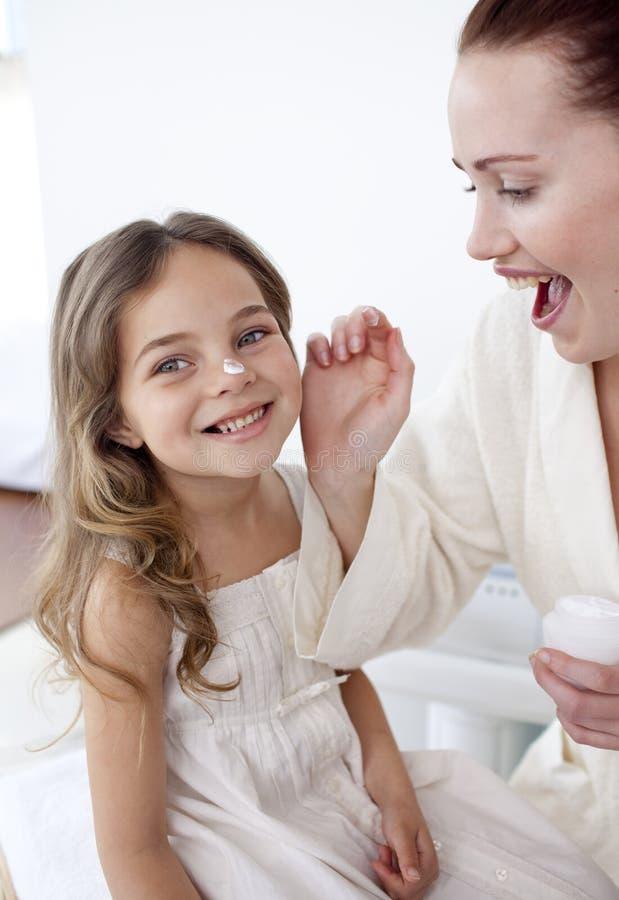 Glückliche Mutter, die Sahne auf Gesicht ihrer Tochter setzt lizenzfreie stockfotografie