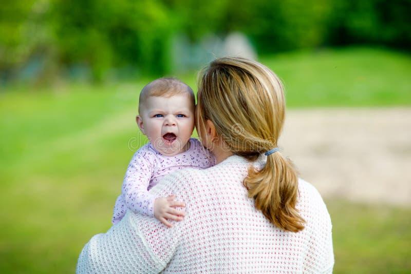 Glückliche Mutter, die Spaß mit neugeborener Babytochter, Familienporträt zusammen hat Mama mit Baby draußen, Liebe neu stockfotografie