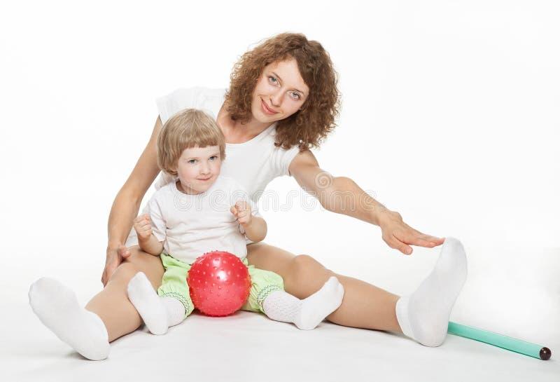 Glückliche Mutter, die Sportübungen mit Tochter tut lizenzfreies stockbild